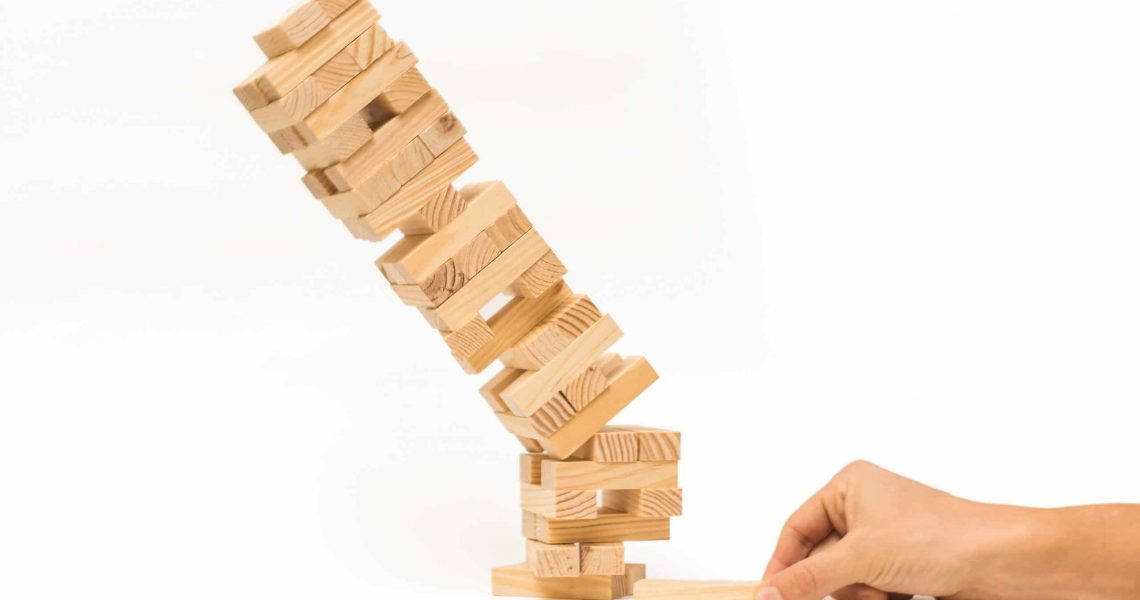 Tower of wooden blocks and man's hand take one block. Jenga game. Isolated tower collapses on white background.