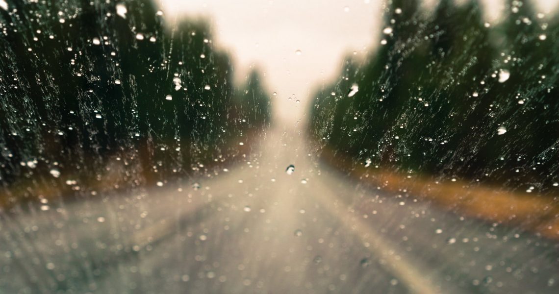 Drops of rain on the window; blurred highway and trees in the background; shallow depth of field